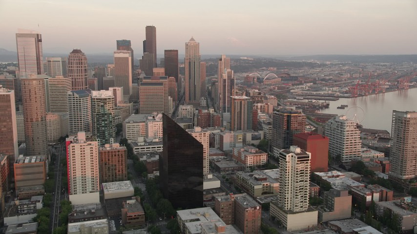 5K stock footage aerial video flyby Downtown Seattle skyscrapers to reveal the Central Waterfront piers, Washington, sunset Aerial Stock Footage | AX50_022