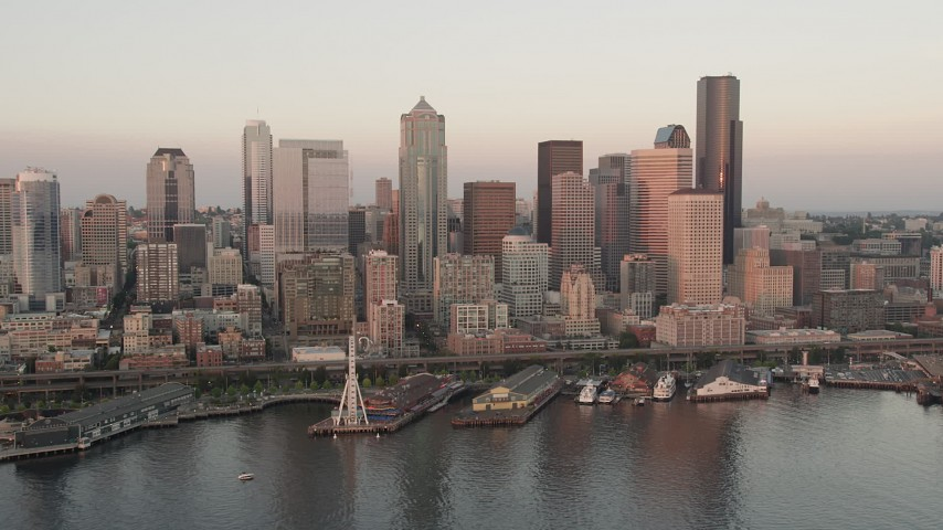 5K stock footage aerial video orbit Downtown Seattle skyscrapers, Alaskan Way Viaduct, and Central Waterfront piers in Washington, sunset Aerial Stock Footage AX50_023