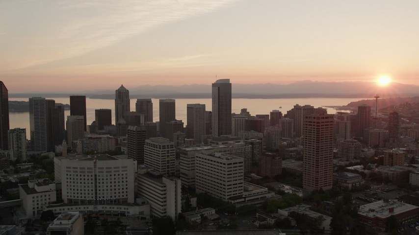 5K stock footage aerial video of flying by Downtown Seattle city buildings with Elliott Bay in the background, Washington, sunset Aerial Stock Footage | AX50_026
