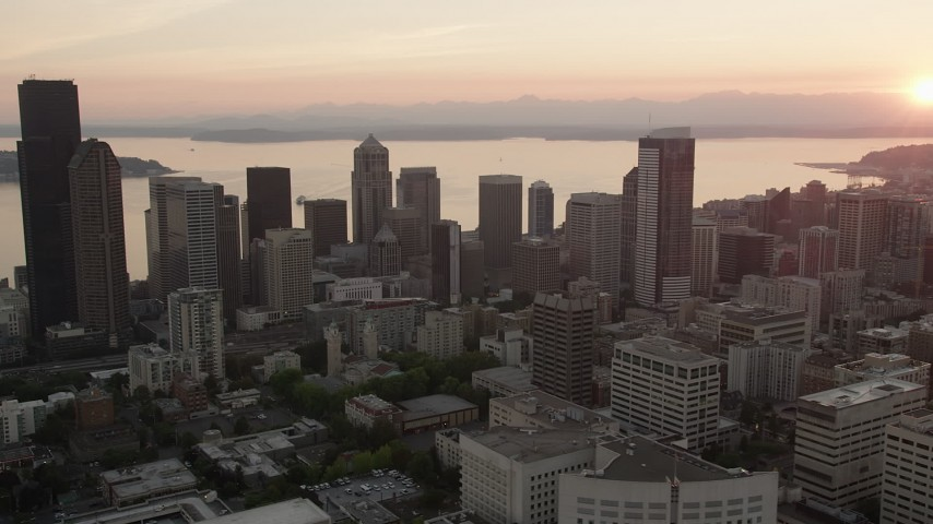 5K stock footage aerial video of passing skyscrapers in Downtown Seattle, Washington, and reveal the setting sun over Elliott Bay Aerial Stock Footage | AX50_027