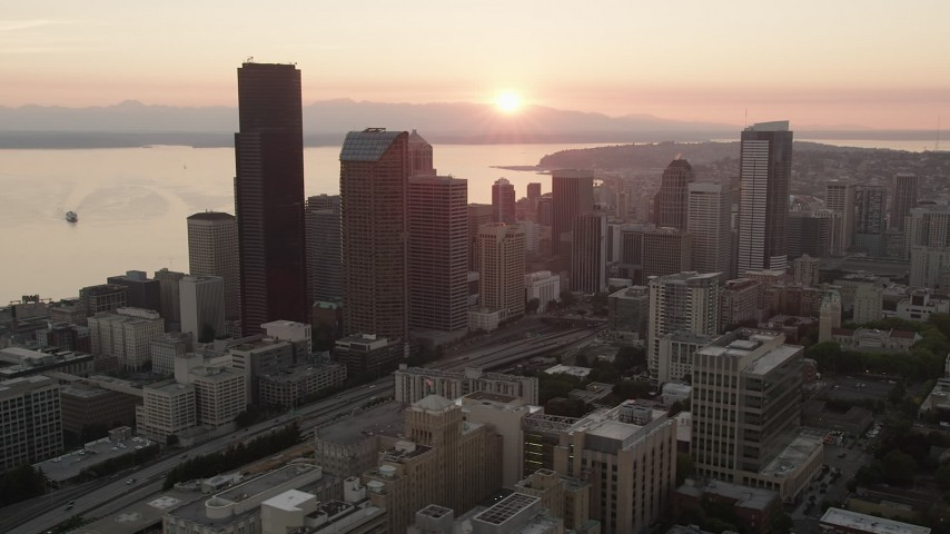 5K stock footage aerial video of passing Downtown Seattle skyscrapers with a view of the setting sun over Elliott Bay, Washington, sunset Aerial Stock Footage | AX50_028