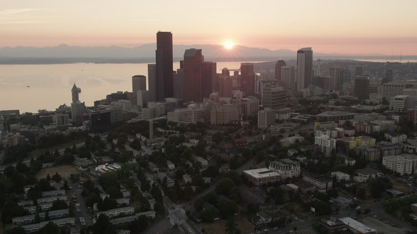 5K stock footage aerial video of Downtown Seattle skyscrapers and high-rises in Washington with the setting sun in the background Aerial Stock Footage | AX50_029