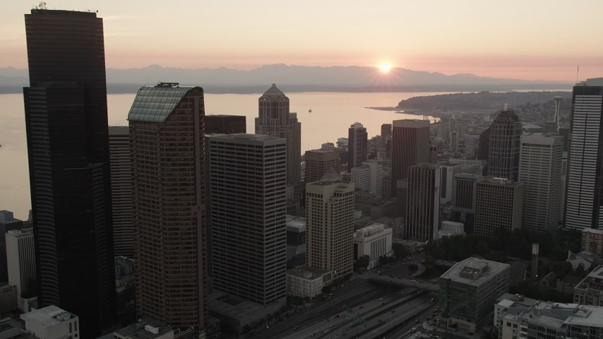 5K stock footage aerial video of skyscrapers toward the setting sun over Elliott Bay, Downtown Seattle, Washington, sunset Aerial Stock Footage | AX50_030