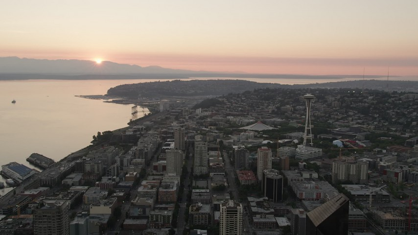 5K stock footage aerial video fly over city buildings to approach KeyArena and the Space Needle at sunset, Downtown Seattle, Washington Aerial Stock Footage | AX50_031