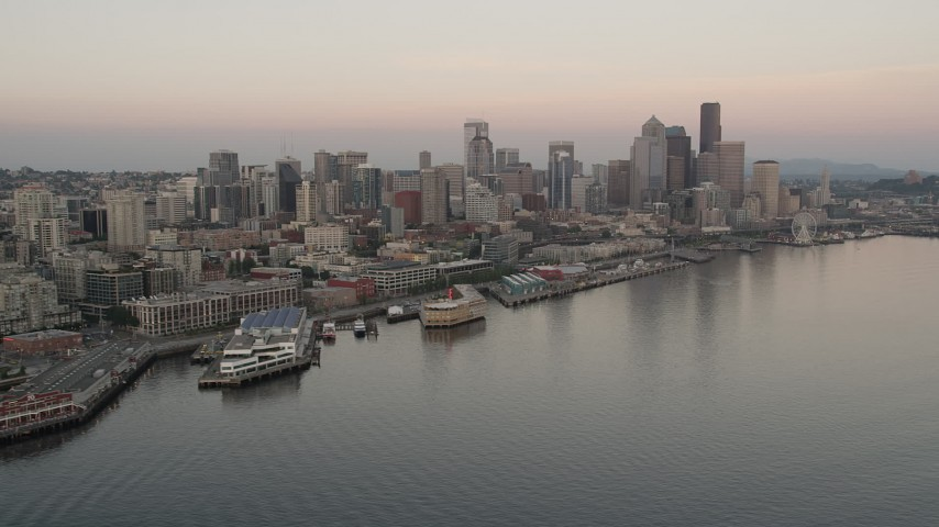 5K stock footage aerial video orbit the Space Needle, skyscrapers, and Central Waterfront piers in Downtown Seattle, Washington, sunset Aerial Stock Footage | AX50_034