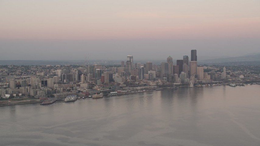 5K stock footage aerial video of Central Waterfront and Downtown Seattle skyscrapers seen from Elliott Bay, Washington, sunset Aerial Stock Footage | AX50_042