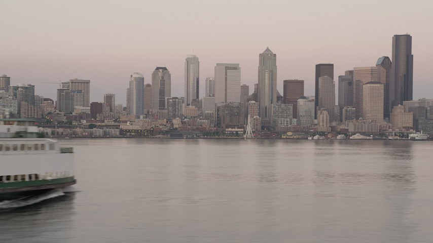 5K stock footage aerial video track a ferry sailing Elliott Bay and reveal the Downtown Seattle skyline in Washington, sunset Aerial Stock Footage | AX50_044