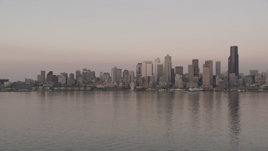 5K stock footage aerial video of view of the Downtown Seattle skyline from Elliott Bay, revealing a ferry sailing the bay, Washington, sunset Aerial Stock Footage | AX50_045