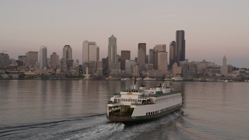5K stock footage aerial video track a ferry sailing Elliott Bay and reveal the Central Waterfront and the Downtown Seattle skyline, Washington, sunset Aerial Stock Footage | AX50_046