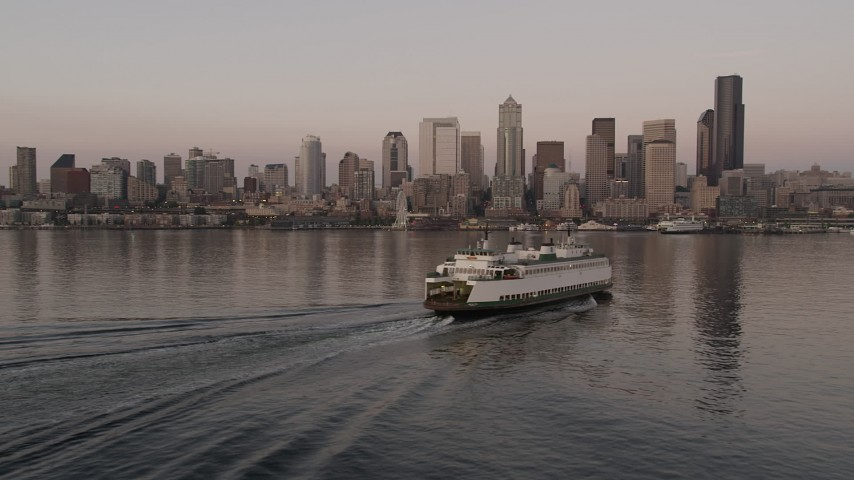 5K stock footage aerial video track a ferry sailing Elliott Bay toward the Seattle Waterfront and Downtown Seattle skyline in Washington, sunset Aerial Stock Footage | AX50_047
