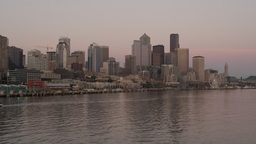 5K stock footage aerial video of low approach to the Great Wheel and Waterfront, and the towering skyline of Downtown Seattle, Washington, sunset Aerial Stock Footage | AX50_049