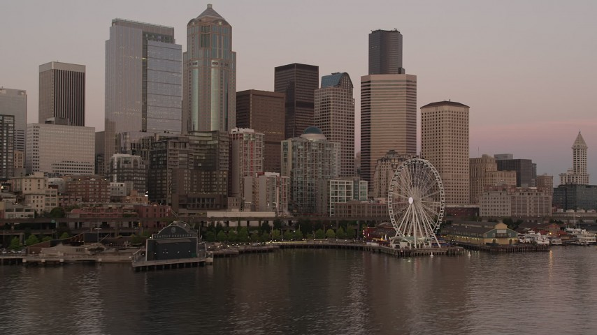 5K stock footage aerial video flyby the Waterfront and Downtown Seattle skyscrapers to focus on the Seattle Great Wheel, Washington, sunset Aerial Stock Footage | AX50_050