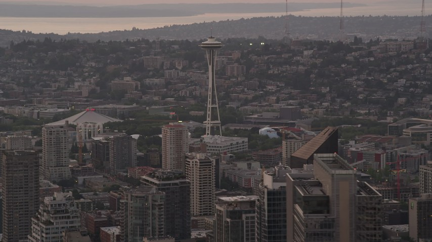 5K stock footage aerial video of Seattle Space Needle seen while passing 1201 Third Avenue Tower in Downtown Seattle, Washington, sunset Aerial Stock Footage | AX50_052
