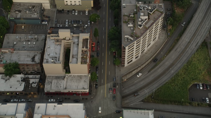 5K stock footage aerial video of bird's eye view of following 1st Avenue through Downtown Seattle, Washington, sunset Aerial Stock Footage | AX50_056