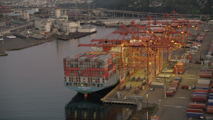 5K stock footage aerial video of passing Harbor Island to approach a fully-laden cargo ship docked at the Port of Seattle, Washington, sunset Aerial Stock Footage | AX50_067