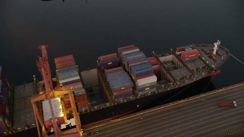 5K stock footage aerial video of flying over cargo ships laden with containers docked beneath cranes at the Port of Seattle, Washington, sunset Aerial Stock Footage | AX50_068