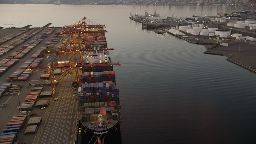 5K stock footage aerial video orbit a cargo ship stacked with shipping containers beneath cranes at the Port of Seattle, Washington, sunset Aerial Stock Footage | AX50_069