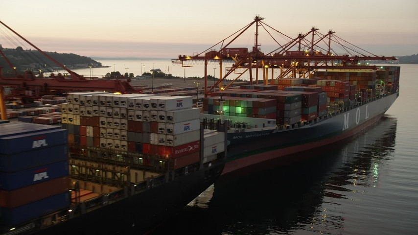 5K stock footage aerial video flyby a pair of loaded cargo ships docked beneath cranes at the Port of Seattle, Washington, sunset Aerial Stock Footage | AX50_070
