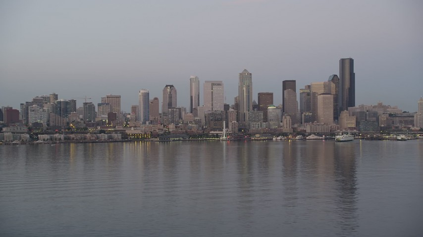 5K stock footage aerial video of a view across Elliott Bay at the Downtown Seattle skyline and Central Waterfront, Washington, sunset Aerial Stock Footage | AX50_072