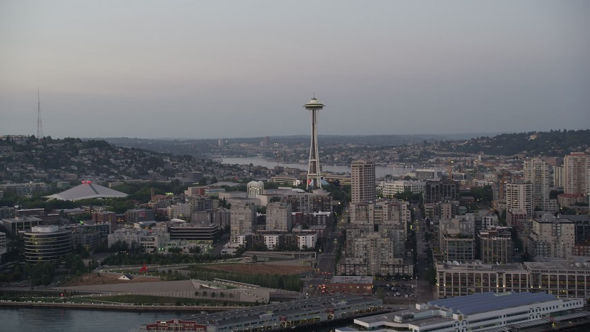 5K stock footage aerial video tilt from Elliott Bay to reveal the Seattle Space Needle and Central Waterfront piers in Downtown Seattle, Washington, sunset Aerial Stock Footage | AX50_073