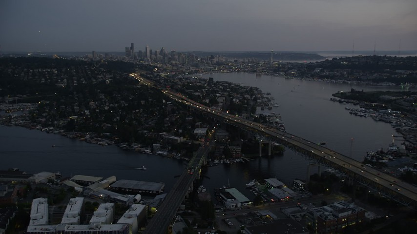 5K aerial  video of Ship Canal Bridge, approach Lake Union and the Downtown Seattle skyline, Washington, twilight Aerial Stock Footage | AX50_087