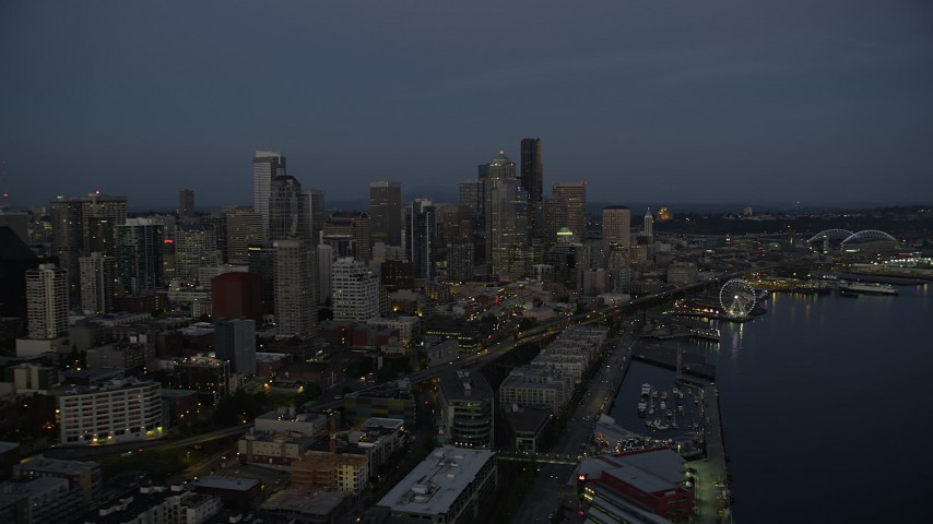 5K stock footage aerial video flyby Downtown Seattle skyscrapers and Seattle Waterfront piers at twilight, Downtown Seattle, Washington Aerial Stock Footage | AX50_091