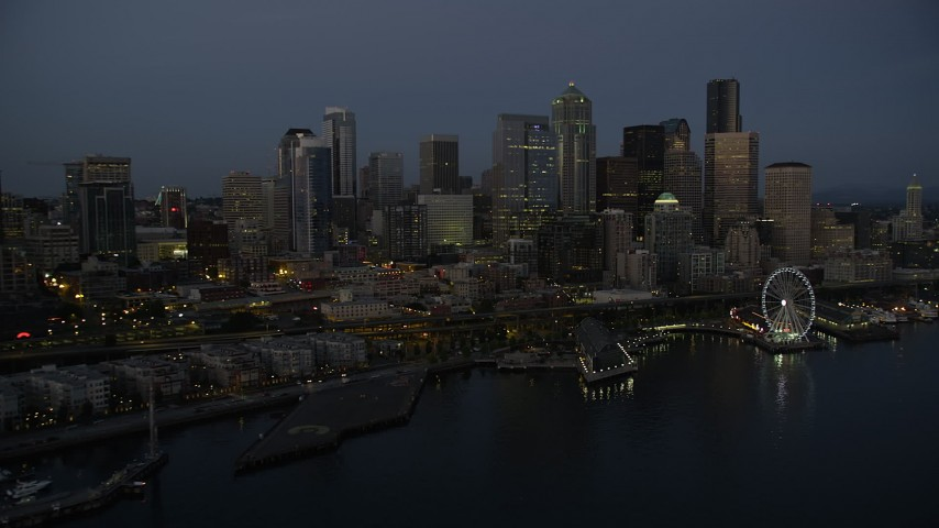 5K stock footage aerial video of passing the Downtown Seattle skyline, Central Waterfront piers and Seattle Great Wheel, Washington, twilight Aerial Stock Footage | AX50_092