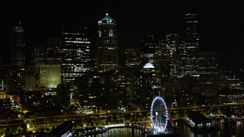 5K stock footage aerial video fly over Great Wheel and Central Waterfront to approach skyscrapers, Downtown Seattle, Washington, night Aerial Stock Footage | AX51_014