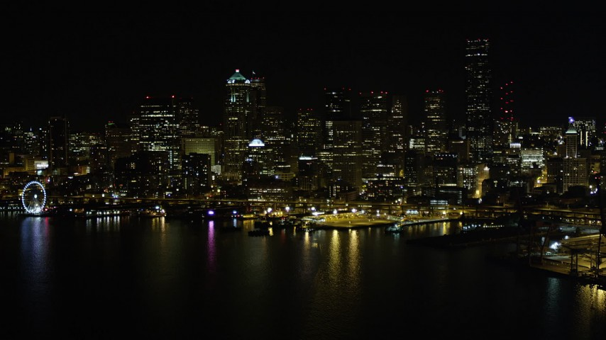 5K stock footage aerial video of Downtown Seattle skyline and Central Waterfront piers, Washington, night Aerial Stock Footage | AX51_016