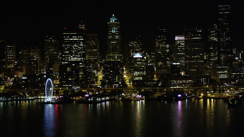 5K stock footage aerial video of Seattle Great Wheel, Waterfront piers, and the Downtown Seattle skyline, Washington, night Aerial Stock Footage AX51_017