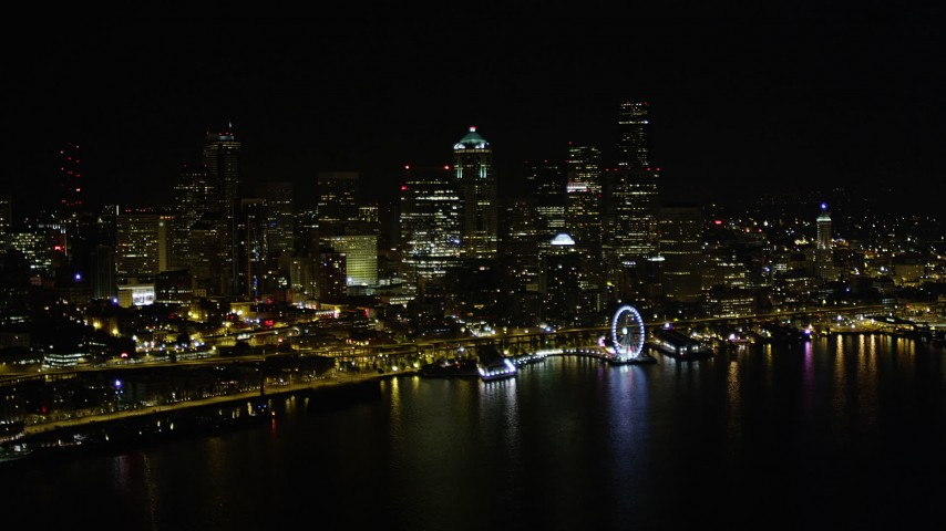 5K stock footage aerial video of the Downtown Seattle skyline, Seattle Great Wheel, and Central Waterfront piers, Washington, night Aerial Stock Footage | AX51_019