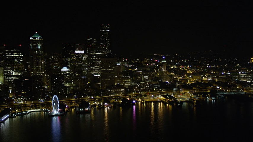 5K stock footage aerial video of Waterfront piers and the Downtown Seattle skysrapers at night, Washington Aerial Stock Footage | AX51_020