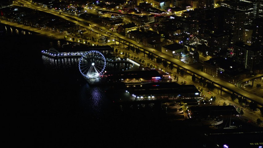 5K stock footage aerial video of Waterfront piers, approach Seattle Great Wheel, Downtown Seattle, Washington, night Aerial Stock Footage | AX51_021