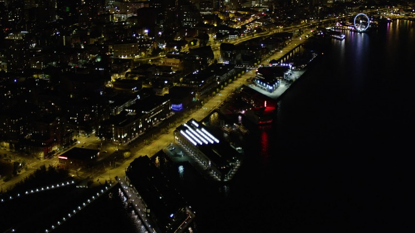 5K stock footage aerial video tilt from Pier 70 to reveal Waterfront and Downtown Seattle skyscrapers, Washington, night Aerial Stock Footage | AX51_024