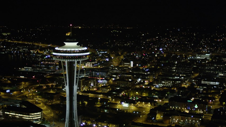 5K stock footage aerial video orbit around the Space Needle towering over city buildings, Downtown Seattle, Washington, night Aerial Stock Footage | AX51_029