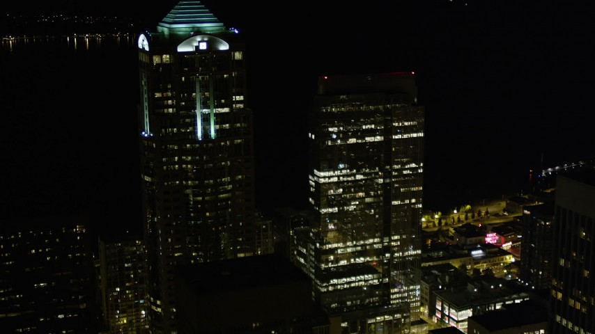 5K stock footage aerial video flyby Downtown Seattle skyscrapers to reveal and track the Seattle Great Wheel at night, Washington Aerial Stock Footage | AX51_039
