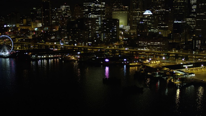 5K stock footage aerial video of Central Waterfront piers near Seattle Great Wheel in Downtown Seattle, Washington, night Aerial Stock Footage | AX51_043
