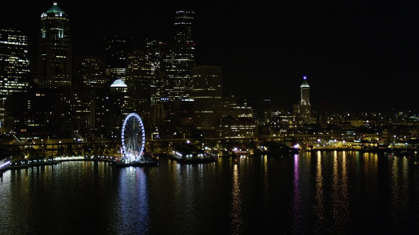 5K stock footage aerial video approach Central Waterfront piers near the Seattle Great Wheel at night, Downtown Seattle, Washington Aerial Stock Footage | AX51_046