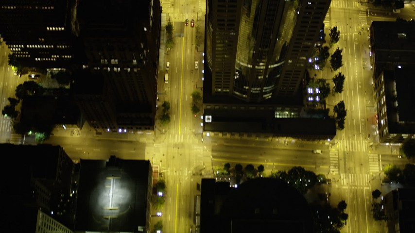 5K stock footage aerial video of bird's eye view following 3rd Avenue past skyscrapers, Downtown Seattle, Washington, night Aerial Stock Footage | AX51_060