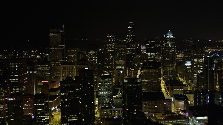 5K stock footage aerial video fly over city buildings to approach taller skyscrapers and high-rises, Downtown Seattle, Washington, night Aerial Stock Footage | AX51_069