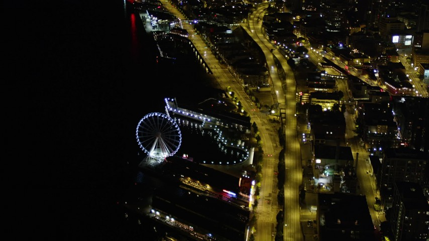 5K stock footage aerial video orbit the Seattle Great Wheel, Central Waterfront piers, and Alaskan Way Viaduct in Downtown Seattle, Washington, night Aerial Stock Footage | AX51_071