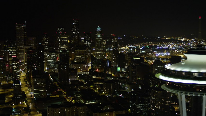 5K stock footage aerial video orbit top of the Space Needle to reveal and focus on Downtown Seattle skyscrapers, Washington, night Aerial Stock Footage AX51_075