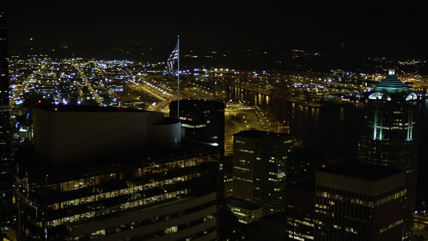 5K stock footage aerial video orbit the American flag atop Two Union Square in Downtown Seattle, Washington, night Aerial Stock Footage | AX51_078