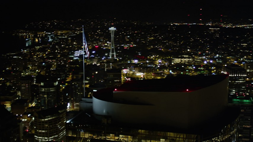 5K stock footage aerial video of an orbit of the American flag on Two Union Square roof in Downtown Seattle, Washington, night Aerial Stock Footage | AX51_079