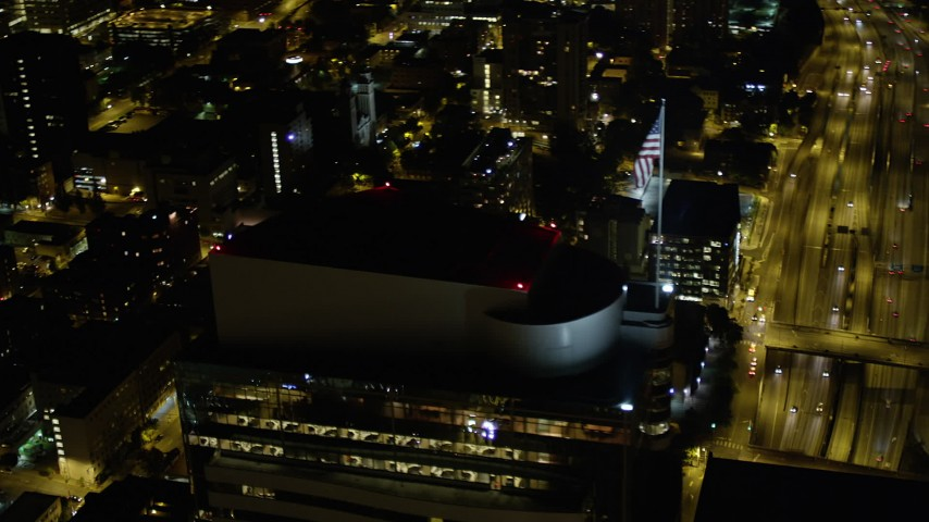 5K stock footage aerial video track American flag on Two Union Square rooftop, Downtown Seattle, Washington, night Aerial Stock Footage | AX51_090
