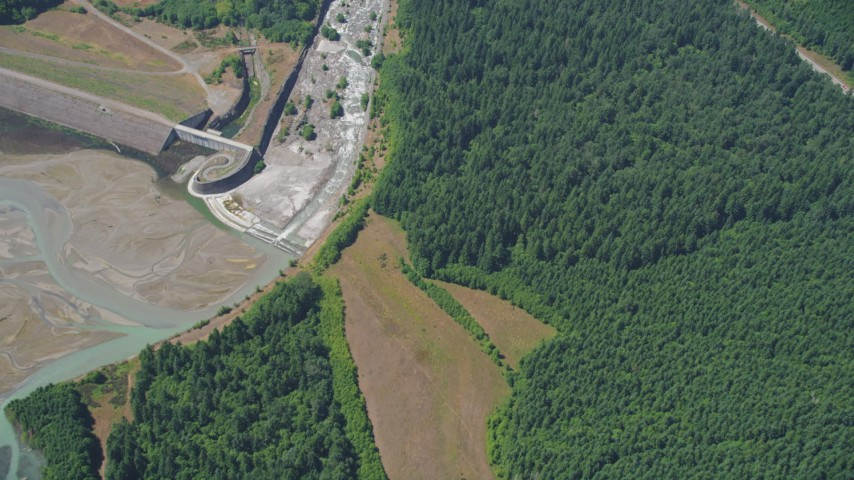 5K stock footage aerial video of North Fork Toutle River beside evergreen forest, reveal a sediment retentions structure dam, Washington Aerial Stock Footage AX52_025 | Axiom Images
