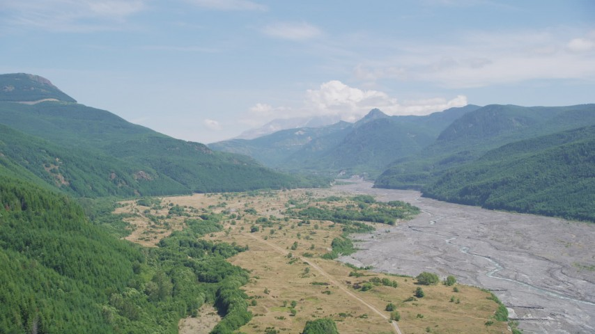5K stock footage aerial video pass a wooded slope to reveal North Fork Toutle River leading to Mount St. Helens, Washington Aerial Stock Footage | AX52_031