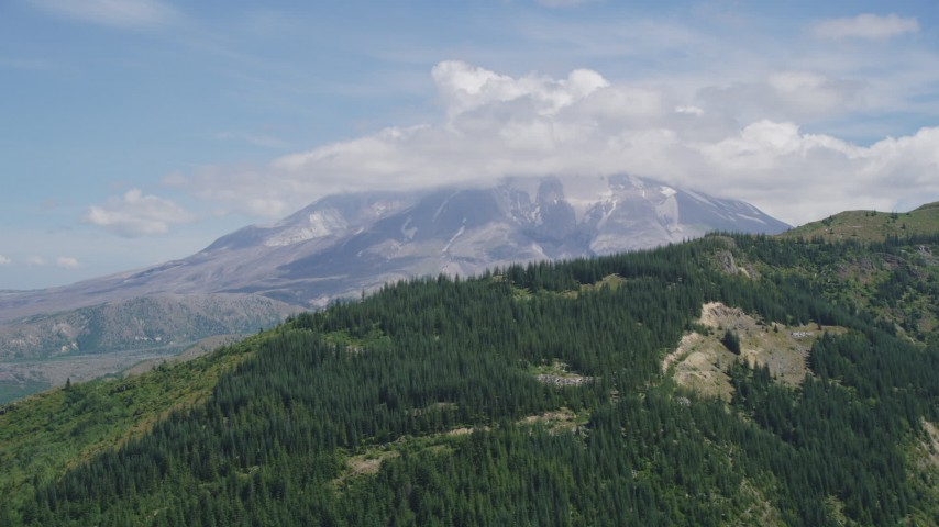 5K aerial video approach Mount St. Helens, capped by clouds, Washington Aerial Stock Footage | AX52_040