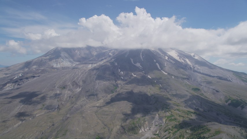 5K aerial video approach cloud-capped Mount St. Helens with patches of snow, Washington Aerial Stock Footage | AX52_046