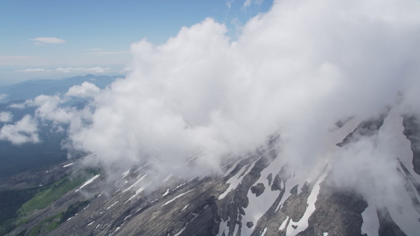 5K aerial video tilt up the snowy slope of Mount St. Helens with summit clouds, Washington Aerial Stock Footage | AX52_055